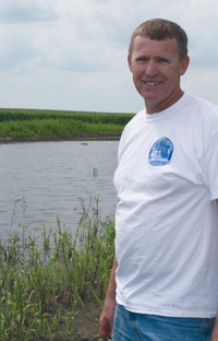 Mike Deahr standing next to wetland on farm