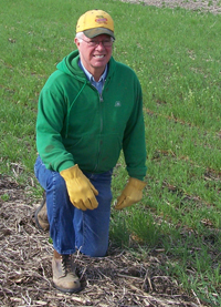 Kelly Tobin kneeling in cover crops